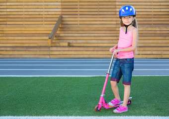 Little girl in helmet with scooter on grass on stadium