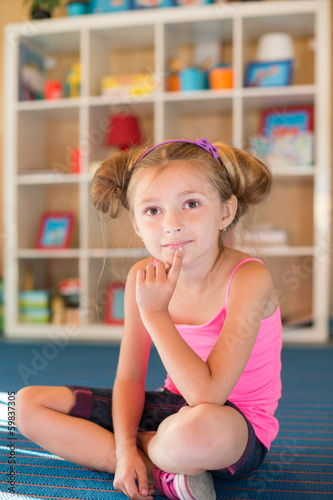 Little girl with thoughtful face sitting on floor playground