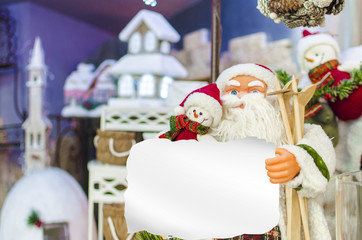 Santa Claus toy holding empty copyspace message paper