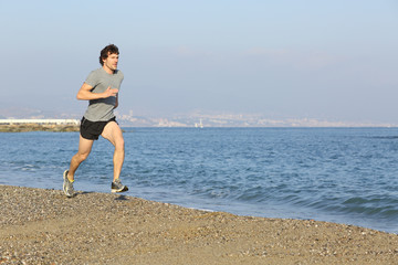 Jogger running on the beach near the water