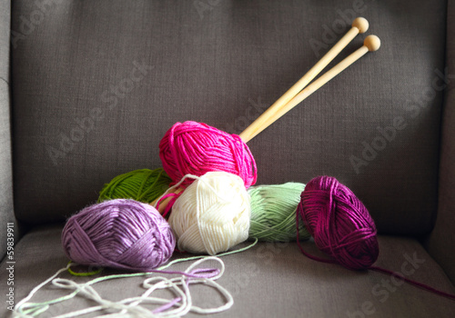 Colorful balls of yarn on the gray armchair
