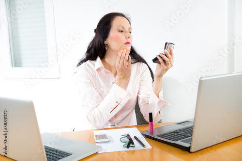 business woman putting some makeup by office work