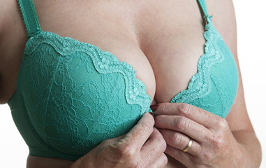 Woman adjusting her green coloured bra