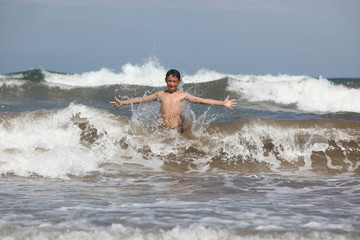boy play with ocean waves