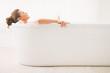 Leinwandbild Motiv Relaxed young woman laying in bathtub
