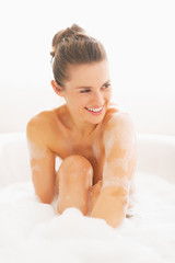 Smiling young woman sitting in bathtub