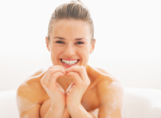 Happy young woman in bathtub showing heart with hands