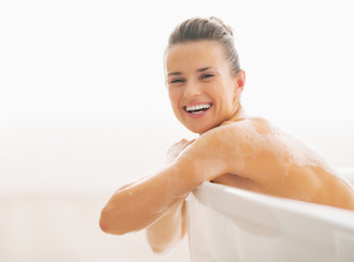 Portrait of smiling young woman sitting in bathtub