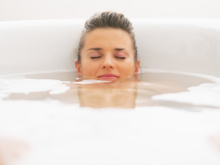 Young woman laying under water in bathtub
