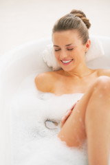 Smiling young woman laying in bathtub