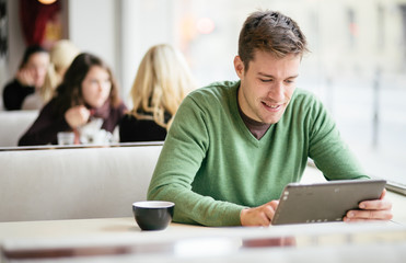 Young man / student using tablet computer in cafe