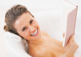 Smiling young woman reading book in bathtub