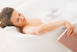 Young woman fall asleep while reading book in bathtub
