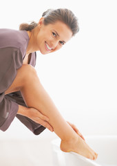 Portrait of happy young woman checking leg skin softness in bath