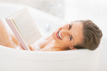 Portrait of smiling young woman reading book in bathtub