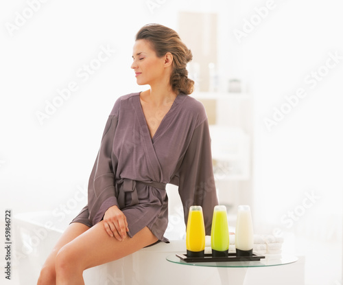 Young woman sitting in bathroom with bath cosmetics
