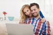 Surprised happy couple looking at laptop