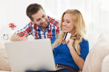 Portrait of couple with laptop and credit card in living room