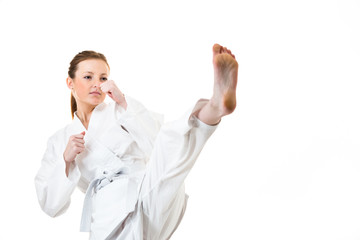 Beautiful caucasian, young, woman makes a kick in karate kimono