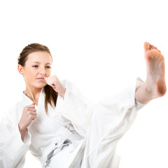 Beautiful caucasian, young, woman makes a kick in karate kimono