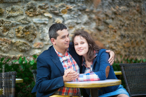 Couple hugging in an outdoor cafe