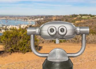 Outdoor daytime viewing telescope on hilltop overlooking harbor