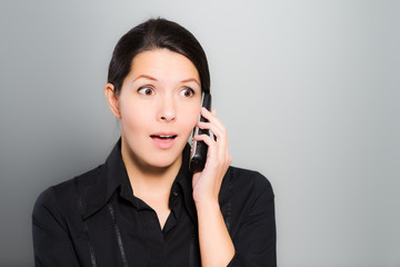Woman reacting in amazement to news on her mobile