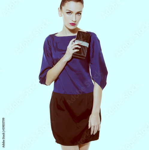fashion model holding little purse in light blue background
