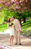 Newlywed couple kissing in park at spring