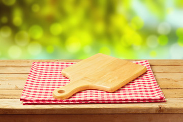 Cutting board on tablecloth on wooden table