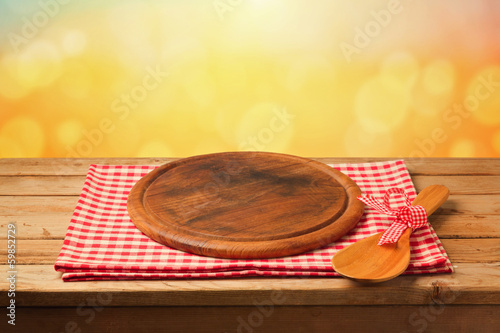Round board on tablecloth on wooden table