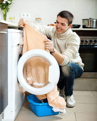 guy  putting clothes in to washing machine