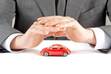 businessman protect with hands a car, concept for costs