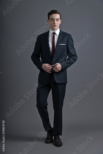 Retro fashion fifties young man wearing dark suit and tie. Studi