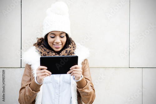 Smiling woman looking tablet computer screen on brown background