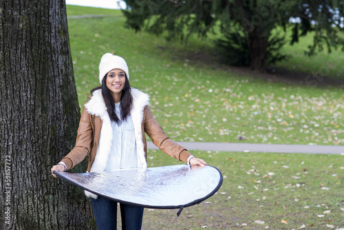 Smiling woman posing at camera and holding reflector, outdoor.