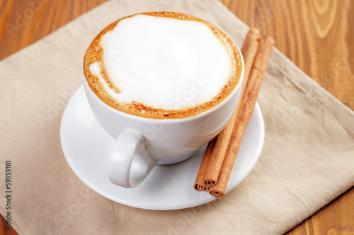 cup of freshly made cappuccino with cinnamon sticks