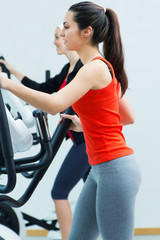 Young people with elliptic machine in the gym
