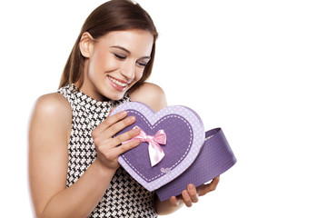 beautiful smiling girl opening a gift box on a white background