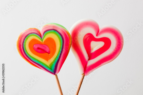 Colorful heart shaped lollipops on grey background