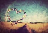 Heart shape made of butterflies on vintage field background