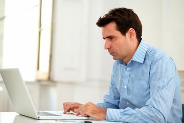 Handsome 30s businessman working with his laptop