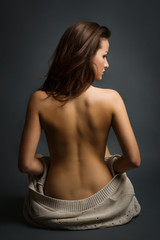 Young beautiful woman, back view, sitting on a floor