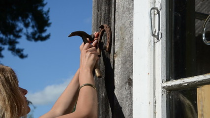 blond girl hammer rusty horse shoe on wooden rural house wall
