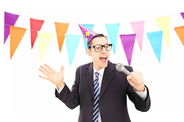 Young male with party hat singing during a celebration