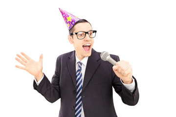 Young man with party hat singing