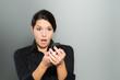 Frau reagiert mit Verwunderung auf den Telefonanruf