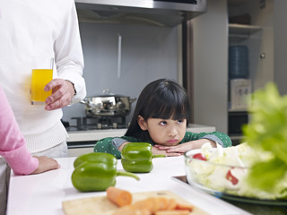 little girl appears to be unhappy in kitchen