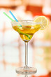 Yellow cocktail in glass on room background
