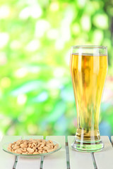 Beer in glass and nuts on table on nature background